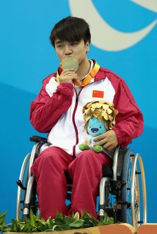 RIO DE JANEIRO, BRAZIL - SEPTEMBER 13: Gold medalist Wenpan Huang of China celebrates on the podium at the medal ceremony for the Mens 50m Freestyle S3 Final during day 6 of the Rio 2016 Paralympic Games at the Olympic Stadium on September 13, 2016 in Rio de Janeiro, Brazil. (Photo by Matthew Stockman/Getty Images)